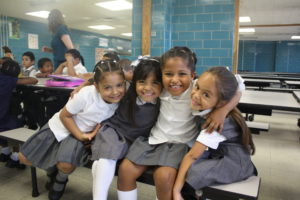 Four young girls hug and smile for the camera as they sit in their classroom.